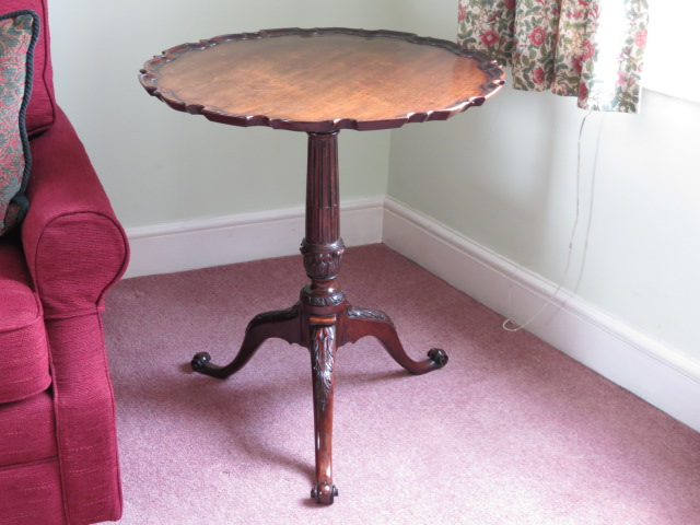 A replica of an ornate 18th century pie crust tripod table.