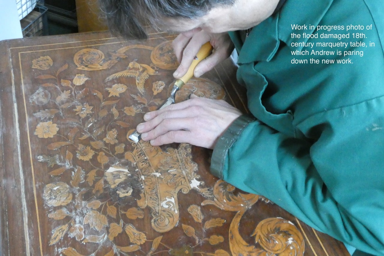 Work in progress photo of the flood damaged 18th century marquetry table, in which Andrew is paring down the new work.
